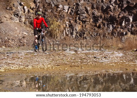 cyclist man riding mountain bike along the puddle in quarry - stock photo