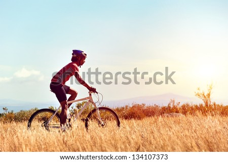 cyclist man riding mountain bike in field horizontal view of healthy lifestyle - stock photo