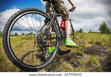cyclist on a Mountain Bike on a forest track. photographed on a fisheye lens. focus on the rear wheel  - stock photo