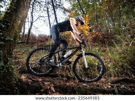 Cyclist on a mountain bike riding in the forest in autumn - stock photo