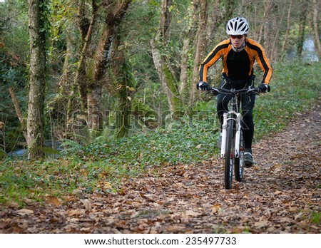 Cyclist on a mountain bike riding in the forest outdoors. - stock photo