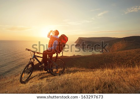 cyclist on a mountain bike stopped to drink water - stock photo