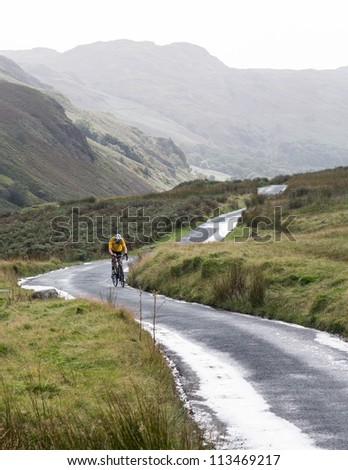 Cyclist on steep hairpin bends on Handknott pass in English Lake District - stock photo