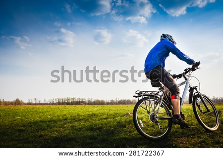 Cyclist on the Beautiful Meadow Trail on sunny day - stock photo