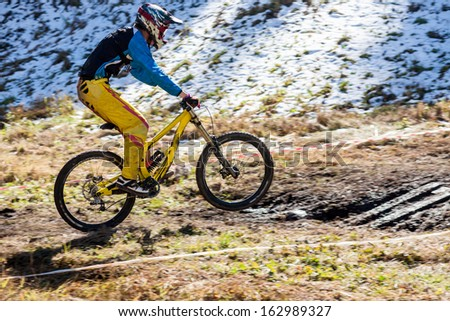Cyclist on the downhill on snow and mud - stock photo