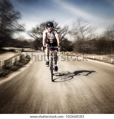 Cyclist on the road touring at speed - stock photo