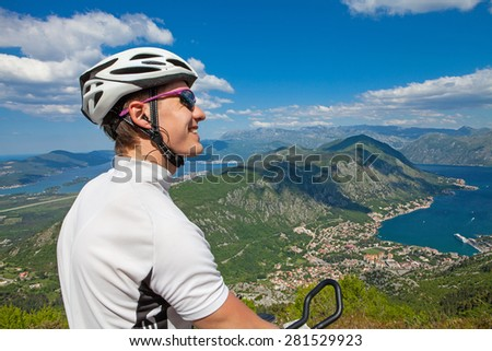 Cyclist on the top of a hill looking away - stock photo