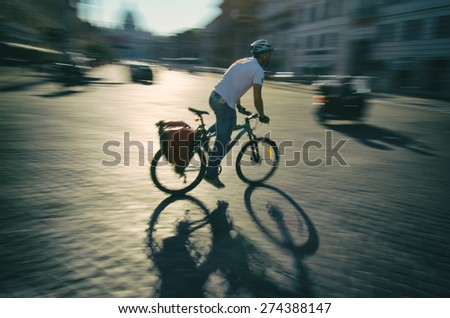 Cyclist passes by in a blur along the traditional cobblestone streets of Rome Italy - stock photo