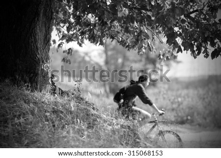 cyclist rides along the road in nature in black and white - stock photo