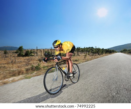 Cyclist riding a bike on an open road in Macedonia with a sun in the background - stock photo