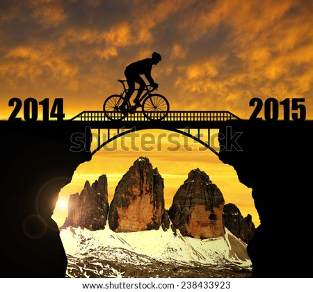 Cyclist riding across the bridge at sunset. In the background Tre Cime di Lavaredo. Forward to the New Year 2015  - stock photo