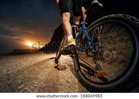 Cyclist riding mountain bike on trail at night. - stock photo