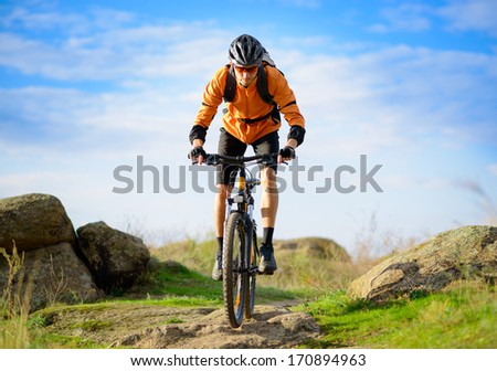 Cyclist Riding the Bike on the Beautiful Spring Mountain Trail - stock photo