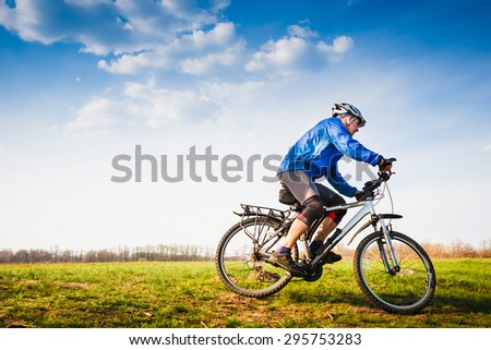 Cyclist Riding the Bike on the Beautiful Summer Meadow trail - stock photo