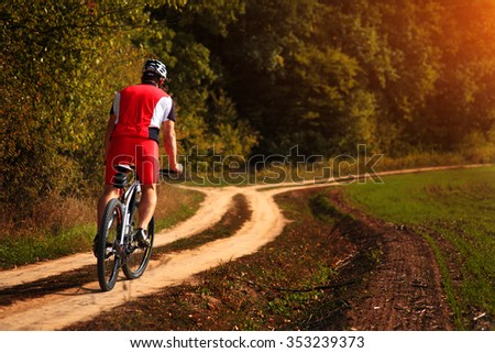 Cyclist Riding the Mountain Bike Down Hill on the Autumn Meadow in the Beautiful Forest - stock photo