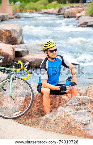 Cyclist takes a break by the river - stock photo