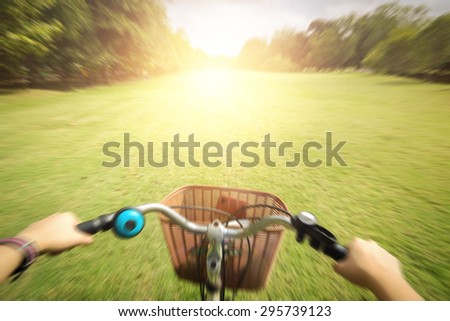 cyclist woman hands on handlebar bike on trail in summer park,vignette,flare - stock photo