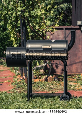 Cylindrical black barbecue with closed cover and smoke pipe in the summer garden of cottage in front view - stock photo