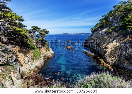 Cypress Cove with its crystal-clear aquamarine waters, surrounded by, unusual geological rock formations and Cypress trees. In the background you Carmel Bay, at point Lobos State Natural Reserve. - stock photo