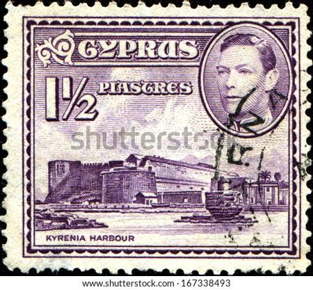 CYPRUS - CIRCA 1938: A stamp printed in Cyprus shows Kyrenia Harbor and King George VI, circa 1938.  - stock photo