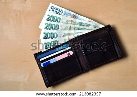 Czech banknotes in leather wallet on the wooden table - stock photo