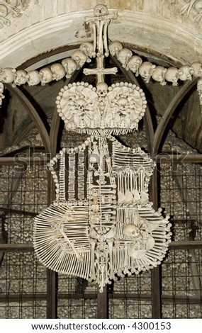 Czech Bone Church. Human bones (skulls, femurs, hips, etc) formed into a family coat of arms at the Kostnice ossuary in Kutna Hora. This macabre display is formed into a family coat of arms. - stock photo