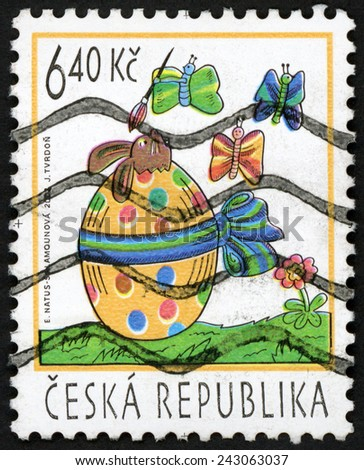 CZECH REPUBLIC - CIRCA 2003: stamp printed in Ceska shows symbols of Easter:  hatching rabbit from painted egg watching three butterflies holding paint brush; Scott 3195 A1224 6.40k, circa 2003 - stock photo