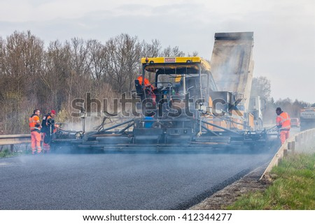 CZECH REPUBLIC, PLZEN, 10 APRIL, 2016: Worker operating asphalt paver machine during road construction and repairing works  - stock photo