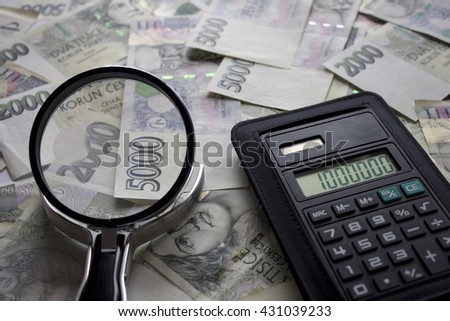 Czech scattered banknotes, calculator and magnifying glass, Czech currency, magnifier as a symbol of the investigation  - stock photo