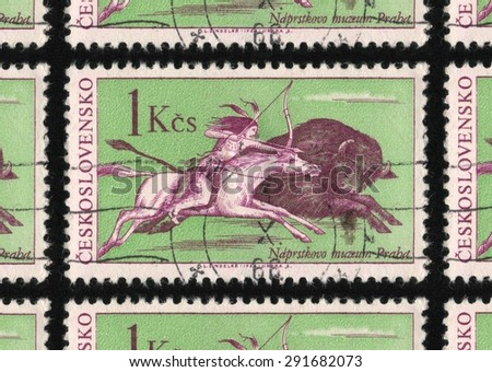 """CZECHOSLOVAKIA - CIRCA 1966: A stamp printed in Czechoslovakia from the """"North American Indians - The 100th Anniversary of the Naprstek's Ethnographic Museum, Prague"""" issue, shows a bison being hunted - stock photo"""