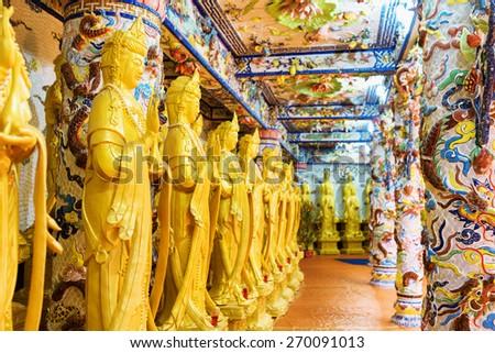 DA LAT, VIETNAM - MARCH 20, 2015: Golden Buddha statues along the wall in the interior of the Linh Phuoc Pagoda in Da Lat city (Dalat), Vietnam. Da Lat is a popular tourist destination of Asia. - stock photo