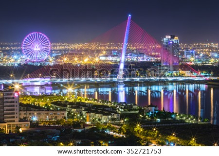 Da Nang, Vietnam, 25th June, 2015: Architecture sail bridge night with the lights of the bridge shaped sails shimmering beneath the city lit up at night makes the city more lively in Danang , Vietnam - stock photo