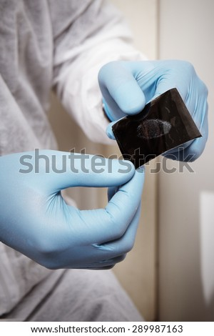 Dactyloscopy - fingerprint lifted after housebreaking - stock photo
