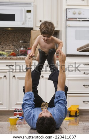 Dad after Work with Toddler on Feet - stock photo