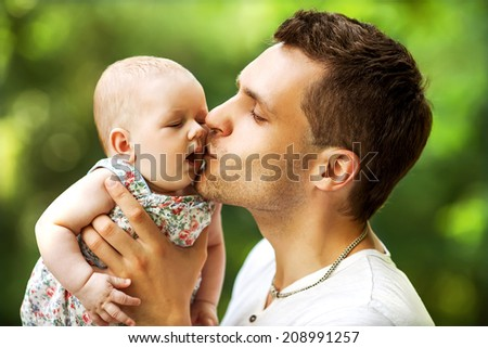 dad and baby daughter playing in the park in love - stock photo