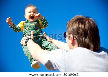 dad and baby son having fan outdoors - stock photo