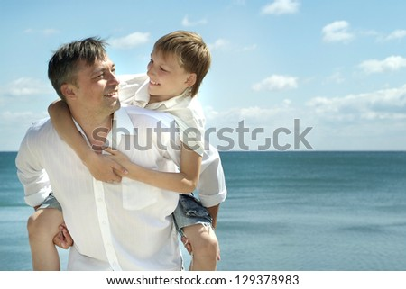 dad and child on the background of the sea - stock photo