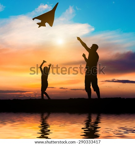 Dad and daughter flying a kite on the beach. silhouette photo - stock photo