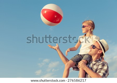 Dad and daughter in sunglasses playing near a house at the day time. Concept of friendly family. - stock photo