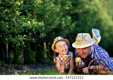 Dad and daughter laughing in a fruit orchard - stock photo