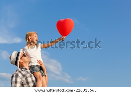 Dad and daughter playing with balloon near a house at the day time - stock photo
