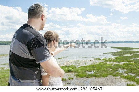 Dad and daughter pointing and looking out at the ocean together - stock photo
