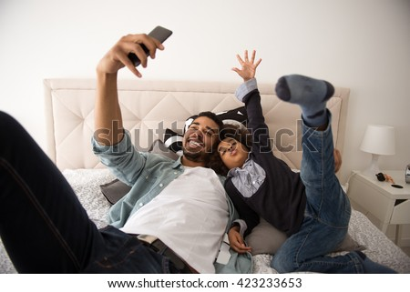 Dad and his cute little girl making a selfie in bed. - stock photo