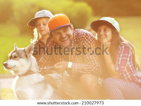Dad and his two daughters in park with dog Husky spend fun time. - stock photo