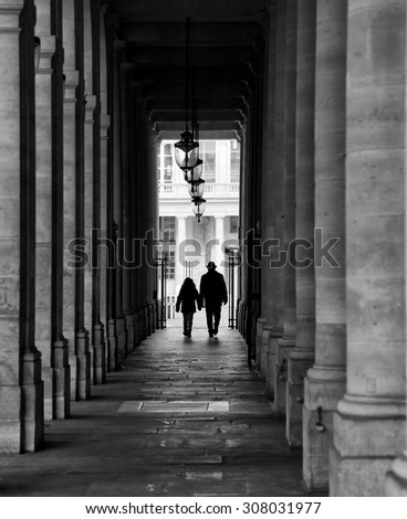 Dad and kid walking in a corridor in Paris.  Black and white picture. - stock photo