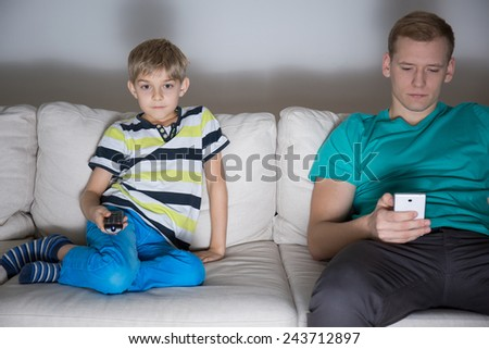 Dad and son addicted to modern technology - stock photo