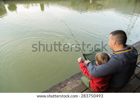 Dad and son go fishing on the lake. - stock photo