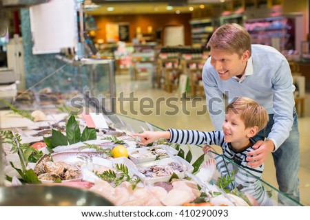 Dad and son in a fish store - stock photo