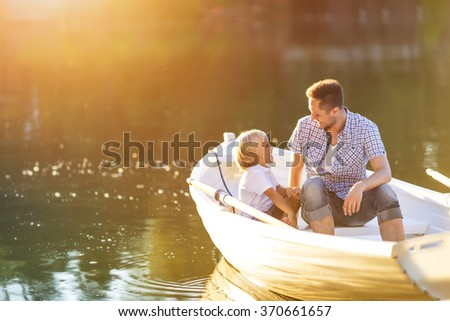 Dad and son in boat on the lake - stock photo