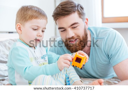 Dad and son playing with toys on bed at home - stock photo